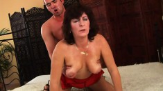 Chubby cougar in a tight red dress gets down with a young lad
