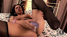 Attractive brunette spreads her legs wide open and drives a dildo deep in her cunt